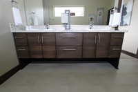 Thumb vanity  contemporary style  quartersawn walnut  dark color  banded door  floating look  legs  banks of drawers  horizontal grain  full overlay
