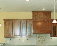 Thumb kitchen  traditional style  knotty alder  medium color  raised panel doors  tall half arch glass doors  angled wood hood with wainscot   6 standard crown  standard overlay