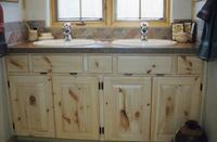 Thumb vanity  traditional style  knotty pine  light color  standard overlay with exposed hinges  small drawers between sink sections