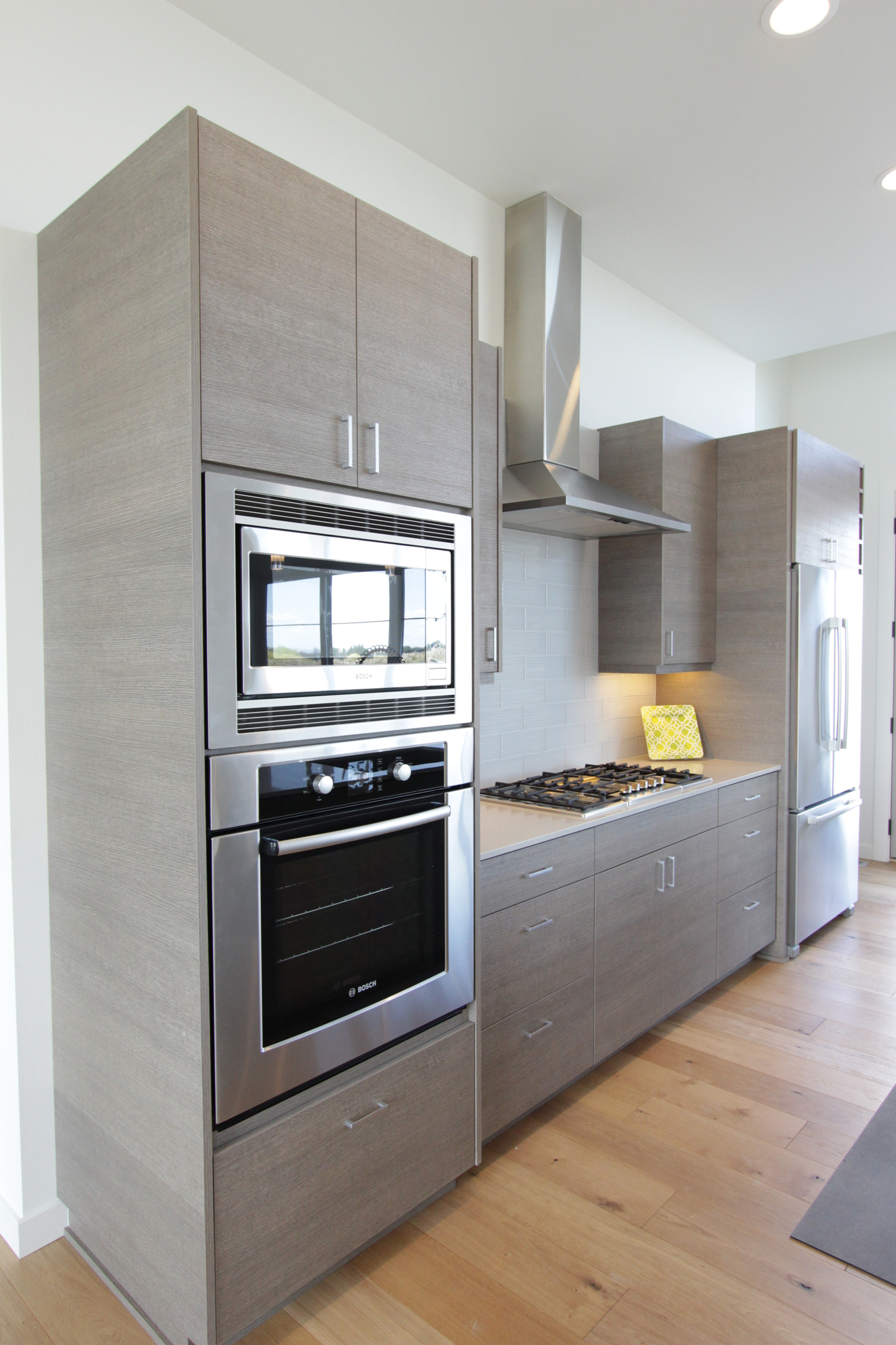 Kitchen  contemporary style  custom laminate  grey   banded door  frameless construction  chimney hood  micro oven cabinet  bank of drawers