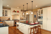 Thumb kitchen  craftsman style  painted  recessed panel  flush mount  glass grid doors  wood hood  butcher block top  turned posts   legs  overhang on the end
