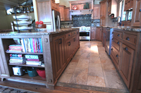 Thumb kitchen  craftsman style  quartersawn oak  medium color  flush mount  island with bookcase  04 wood hood  appliance garage  diagonal corner cabinets  posts  legs  with wood pegs