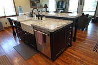 Thumb kitchen  rustic style  black painted island with sand through  apron sink  raised bar with turned posts legs  plant on door on end of the island