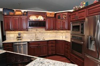 Thumb kitchen  traditional style  cherry  raised panel  cherry color  half arch glass doors  double oven  staggered heights  plate rods