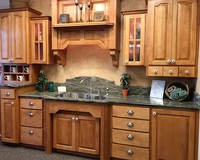 Thumb kitchen  traditional style  hard maple  medium color  raised panel  distressed  half arch doors  hood above sink  glass grid doors with seeded glass  posts   arch at sink front  cubbies  small drawers at bottom