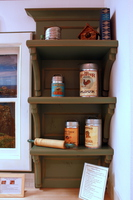 Thumb kitchen  traditional style  knotty alder  green paint with sand through and distress  thick shelves with supports  shelves with corbels  recessed panel back  baking center   30 crown
