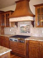 Thumb kitchen  traditional style  knotty alder  medium color  raised panel with arch  curved wood hood  turned posts   legs by rangetop  glass grid doors  standarad overlay
