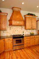 Thumb kitchen  traditional style  knotty alder  medium color  raised panel  angled wood hood  accent color moldings glazed  staggered heights  standard overlay