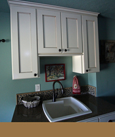 Thumb laundry or utility  traditional style  painted with glaze  recessed panel  short upper above the sink  standard overlay